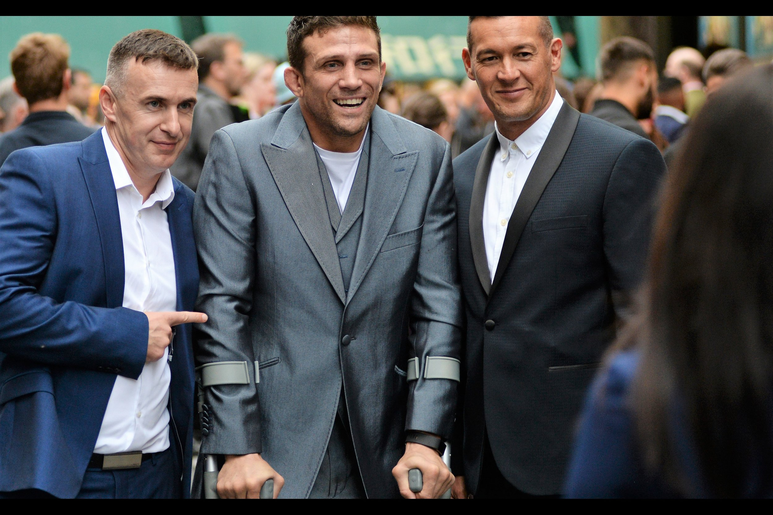 Alex Reid, the subject of the handshake, is a (former?) cage fighter. The crutches are not a result of the prior man's handshake and/or high-five. Or at least I don't think so?