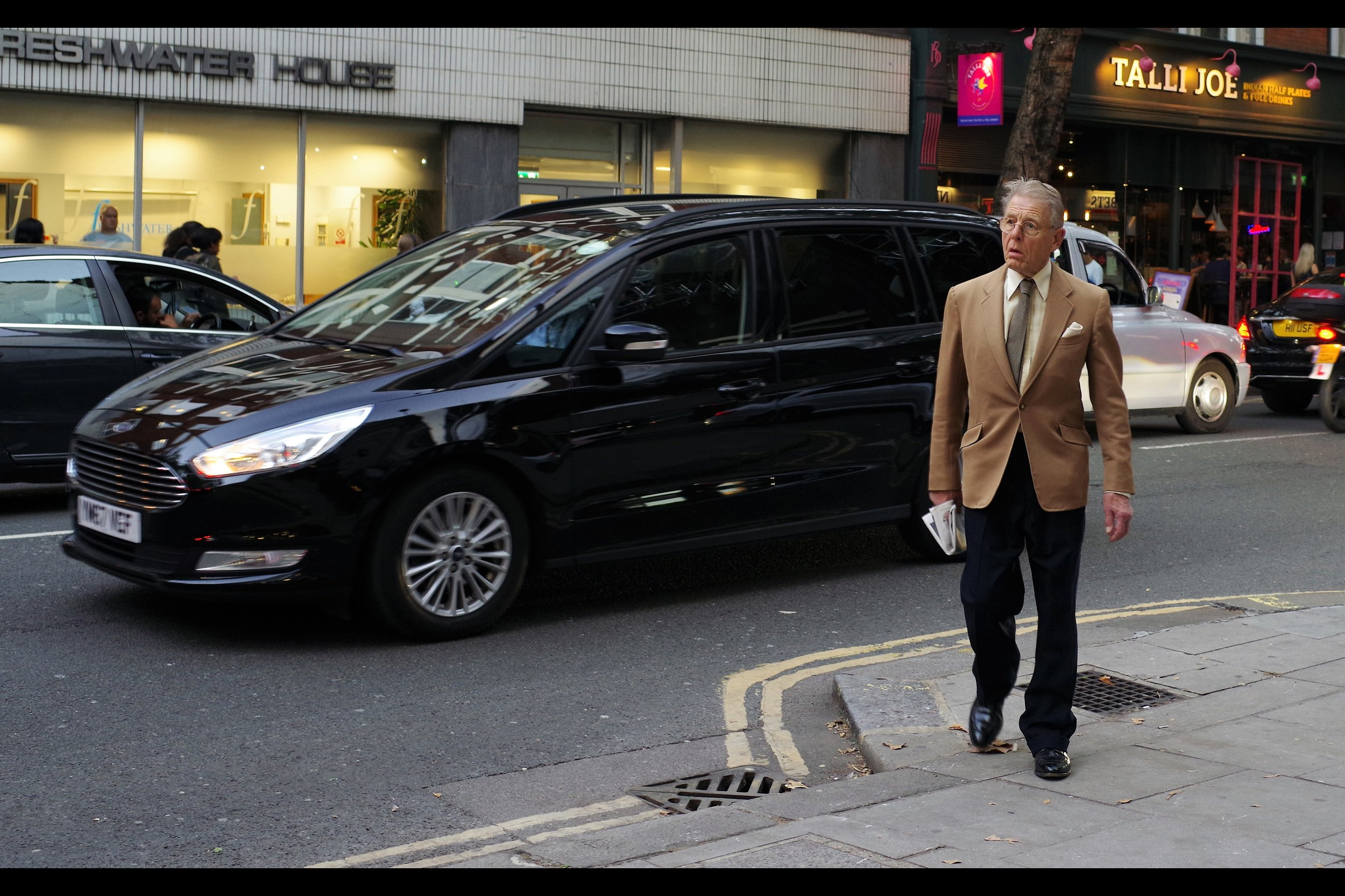 "Our first arrival …. arrives by crossing a road. Edward Fox has won both a film Bafta and TV Bafta, and was ""M"" in the James Bond film ""Never Say Never Again"". He's not in this movie, but he's father to somebody who is."
