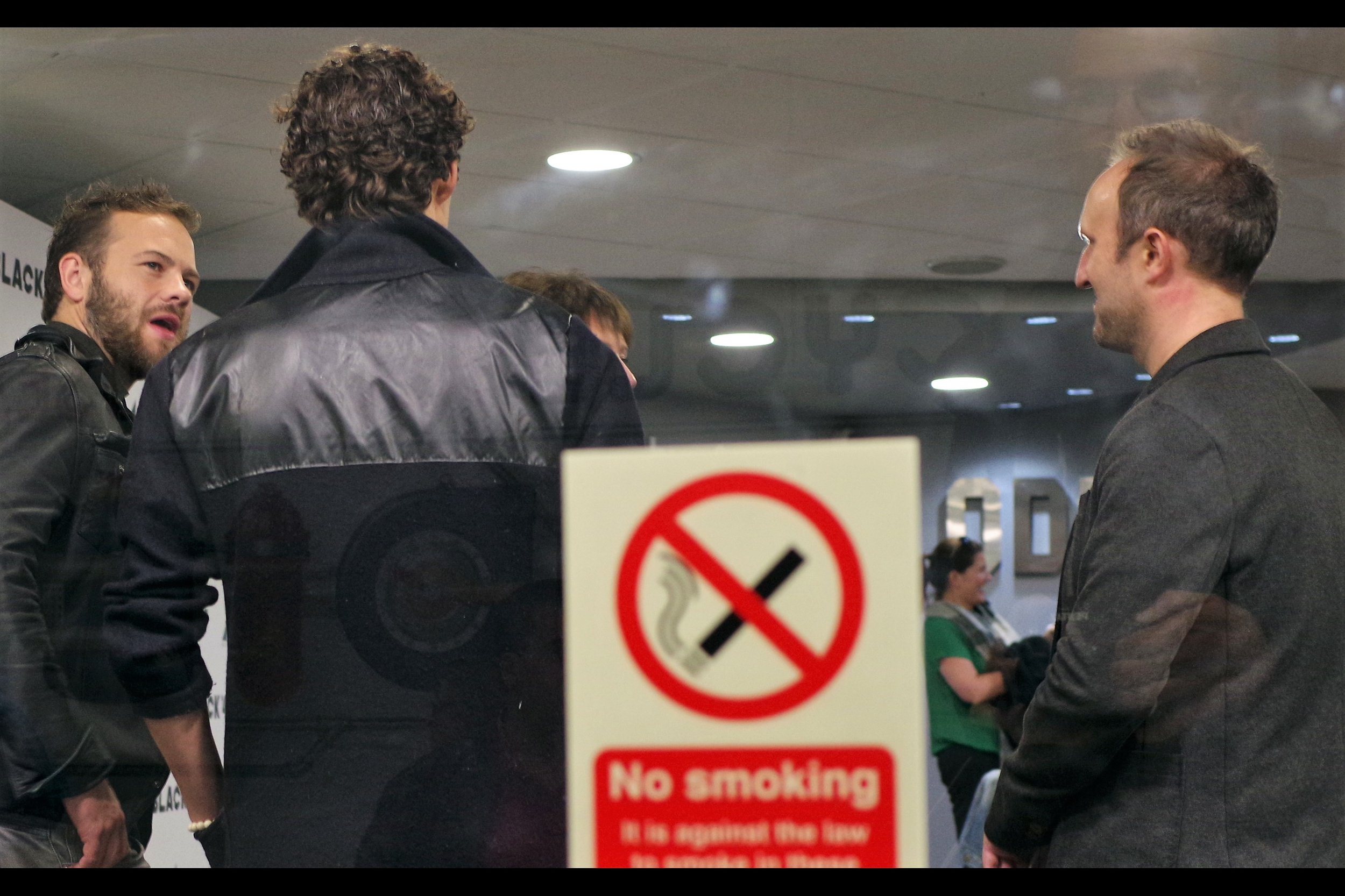 I think the man at far left is Moe Dunford, and if so he's in this movie and I'm sorry he's a bit obscured. But not smoking is also very important and even if blurry I think this sign is relevant.