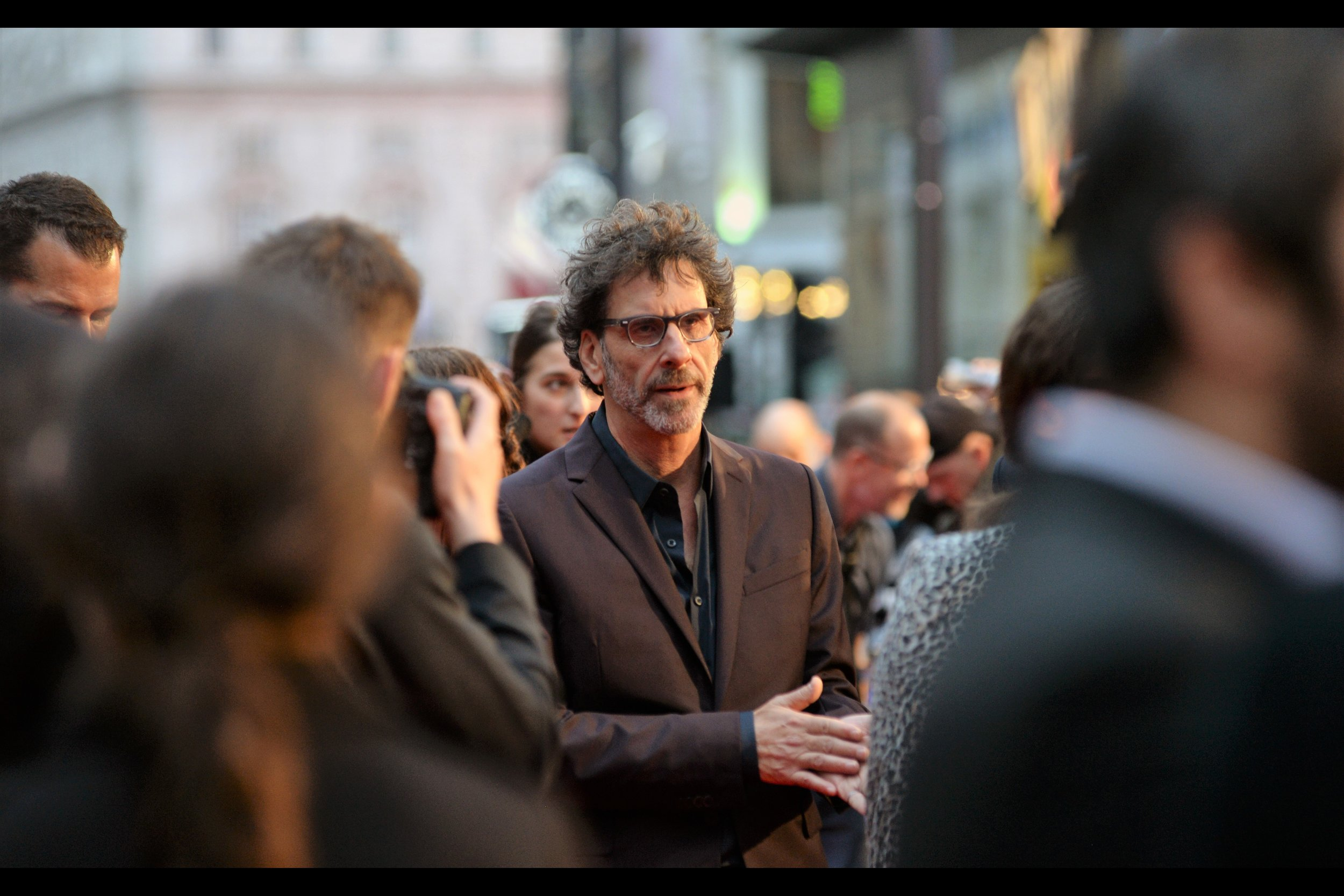 Having posed for the VIP Paparazzi, and possibly not bothered with the regular photographers (?), directors Joel Cohen (pictured) and Ethan Coen (not pictured) decided not to do interviews, let alone sign or pose for selfies or bless babies or politely decline offered spec scrips. And their wide retinue moved as one mass down the red carpet, blocking most shots.