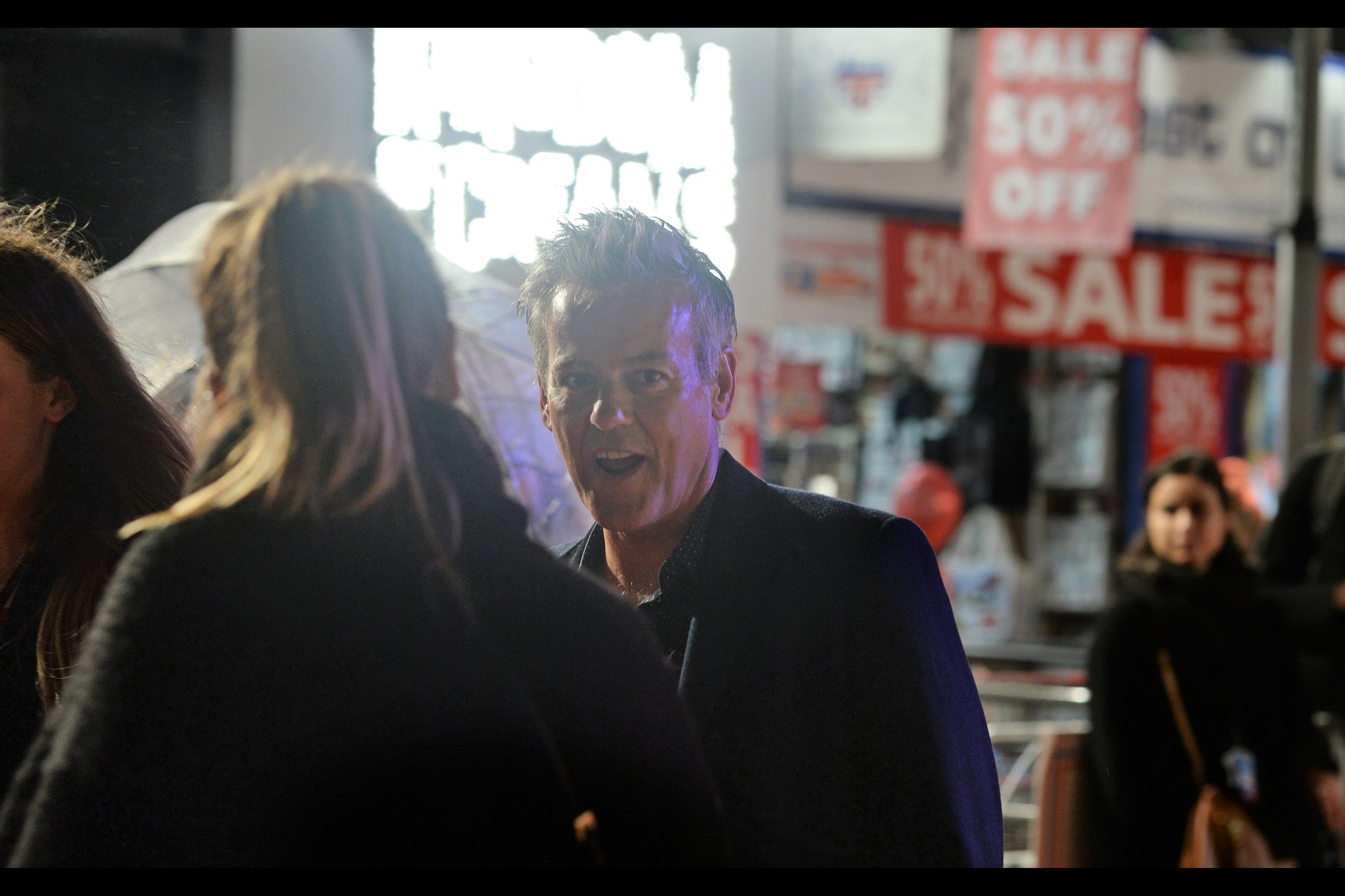 """I don't know who this is, but the Paparazzi did photograph him, and also he's in front of what's fast becoming my favorite Leicester Square backdrop: the Crest of London  """"50% SALE""""  signage."""