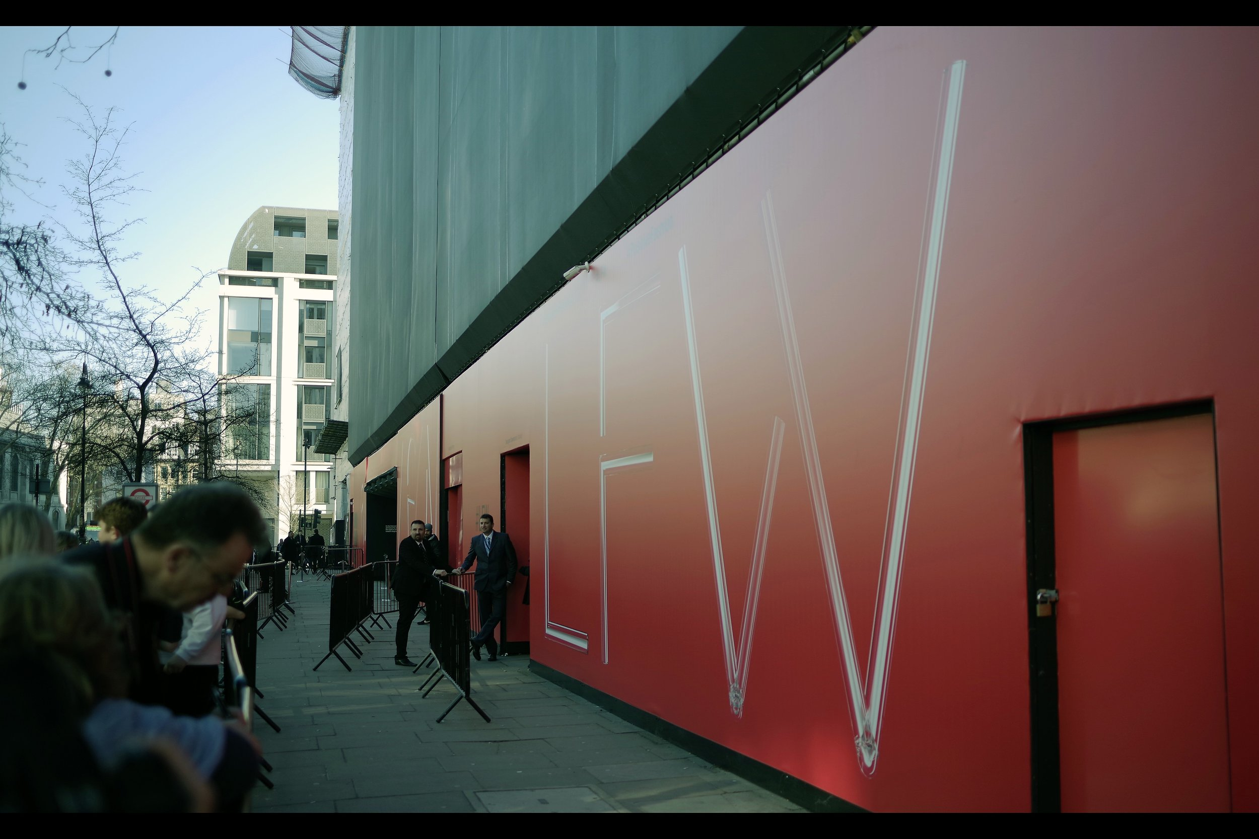 """Yeah, some lout just came along and used his car keys to scratch our nice red wall. Frankly, I think it's a miracle that if you look at the marks a certain way they appear to spell out the letters of London Fashion Week.. but that's just a lucky coincidence…."""