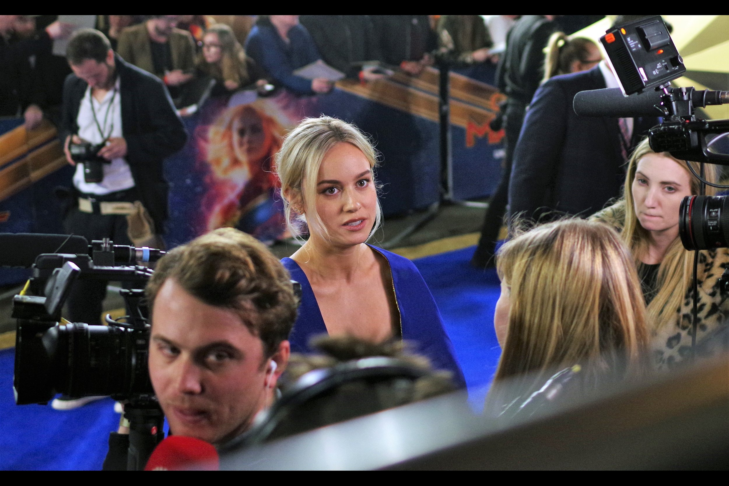 So basically the only thing wrong with this photo of Brie Larson's face sharp in the foreground with the face of Captain Marvel in the background is… everything. There's a dude looking over his shoulder, a guy in a white polo shirt in the background chimping shots on his DSLR, leopard-print lady looking worriedly at the reporter whose hair takes up more photographing real estate than Brie Larson's face. That's photography.