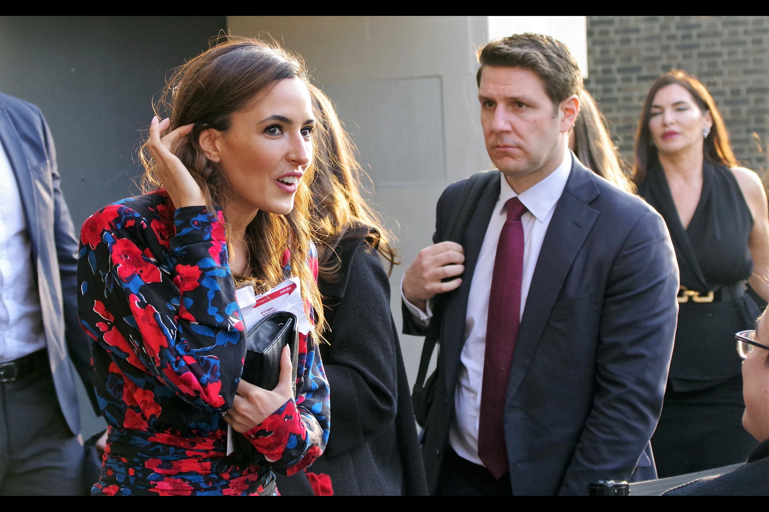 I don't know who Nadia Forde is. Or why that man in the background is looking so glum. I mean.. sure, I'd NEVER have worn a suit and tie to this event if I had a leather jacket and neck tattoos handy instead, but that's a mistake he can hopefully bounce back from.