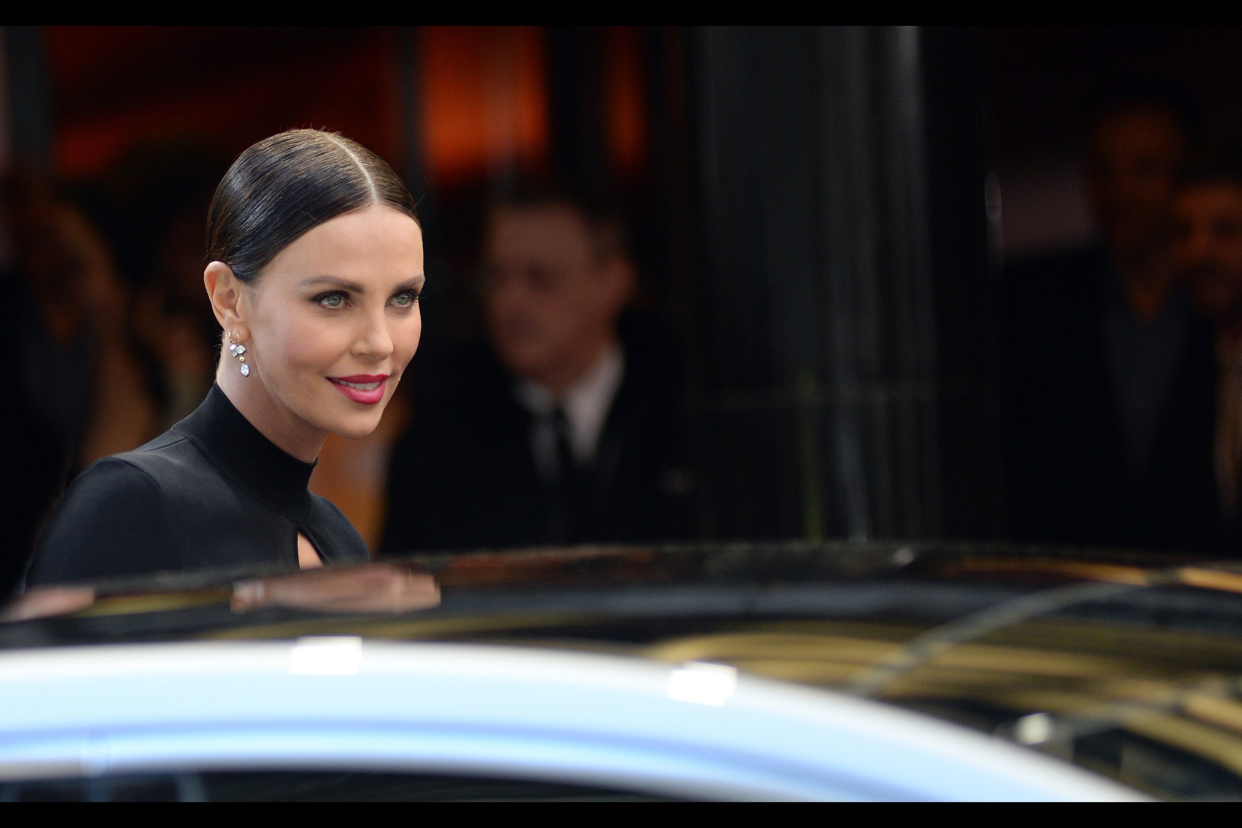 I was a bit sad that Charlize Theron didn't look in my direction before entering the car, like she did for the Paparazzi to my right…. but the more I look at this shot, the less certain I am that it's friendly.