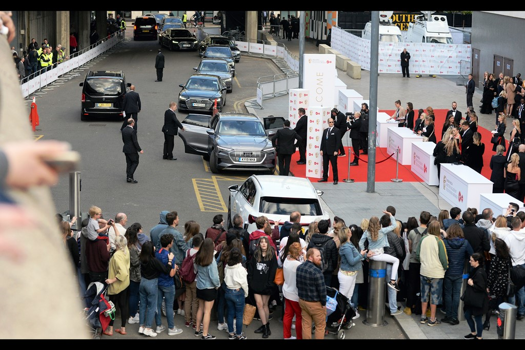 The event is underway, and the dropoff zone is like an airport with planes stacked for landing, dispensing their cargo to the watching eyes of the crowd, photographers and anyone coincidentally on the red carpet who has not been turfed off it for being there without authorisation.