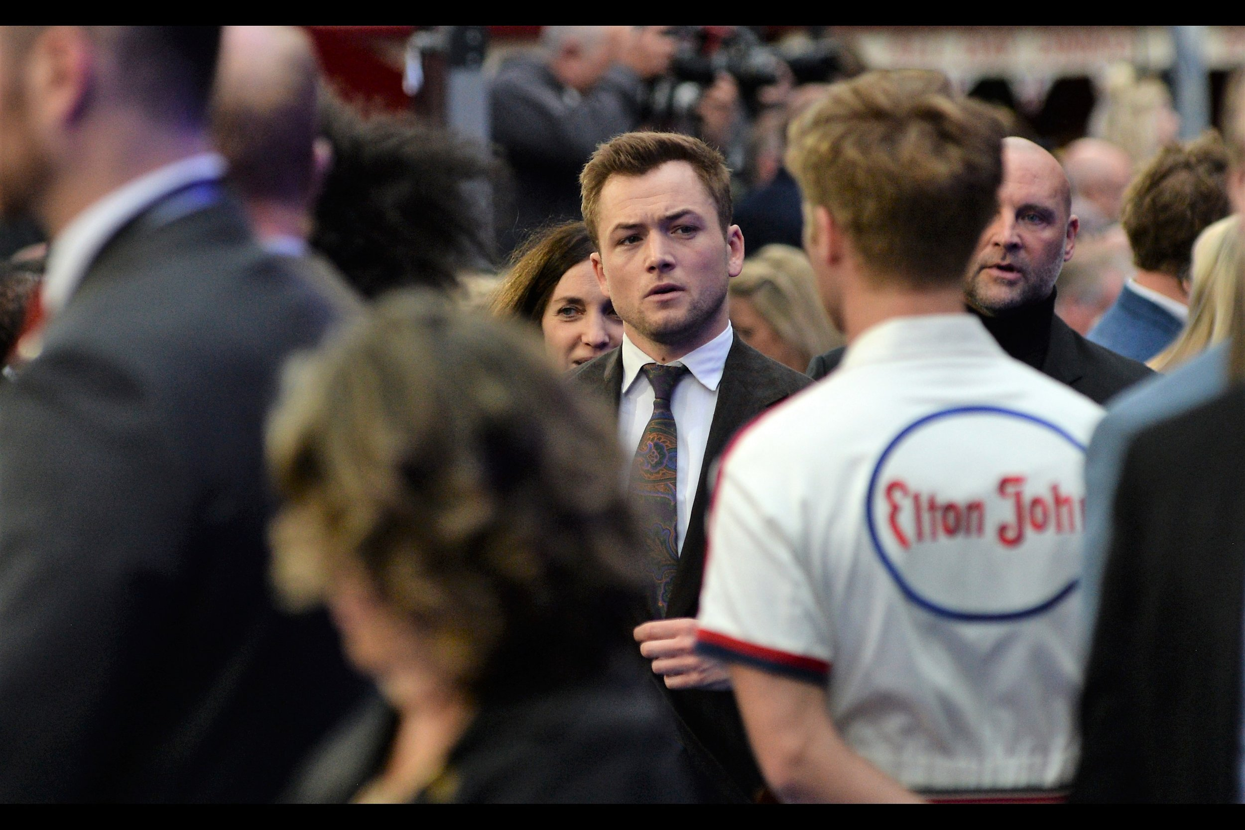 """What do you have written on the back of the shirt…it had better not be what I think it is…""  Taron Egerton, along with actually singing Elton's songs in this biopic, has notably been in the Kingsman series of films (   ""The Secret Service""    and    ""The Golden Circle""   ) at neither of which I photographed him particularly well."