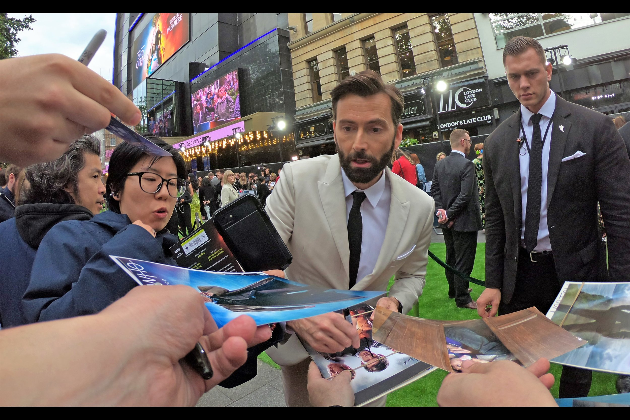 David Tennant briefly signs, and I just want to say that I am standing in the middle of this view and not one of these hands in the photo are mine. It shouldn't be possible… but it is. And I'm happy because those hands are protecting me from the possible wrath of David Tennant.