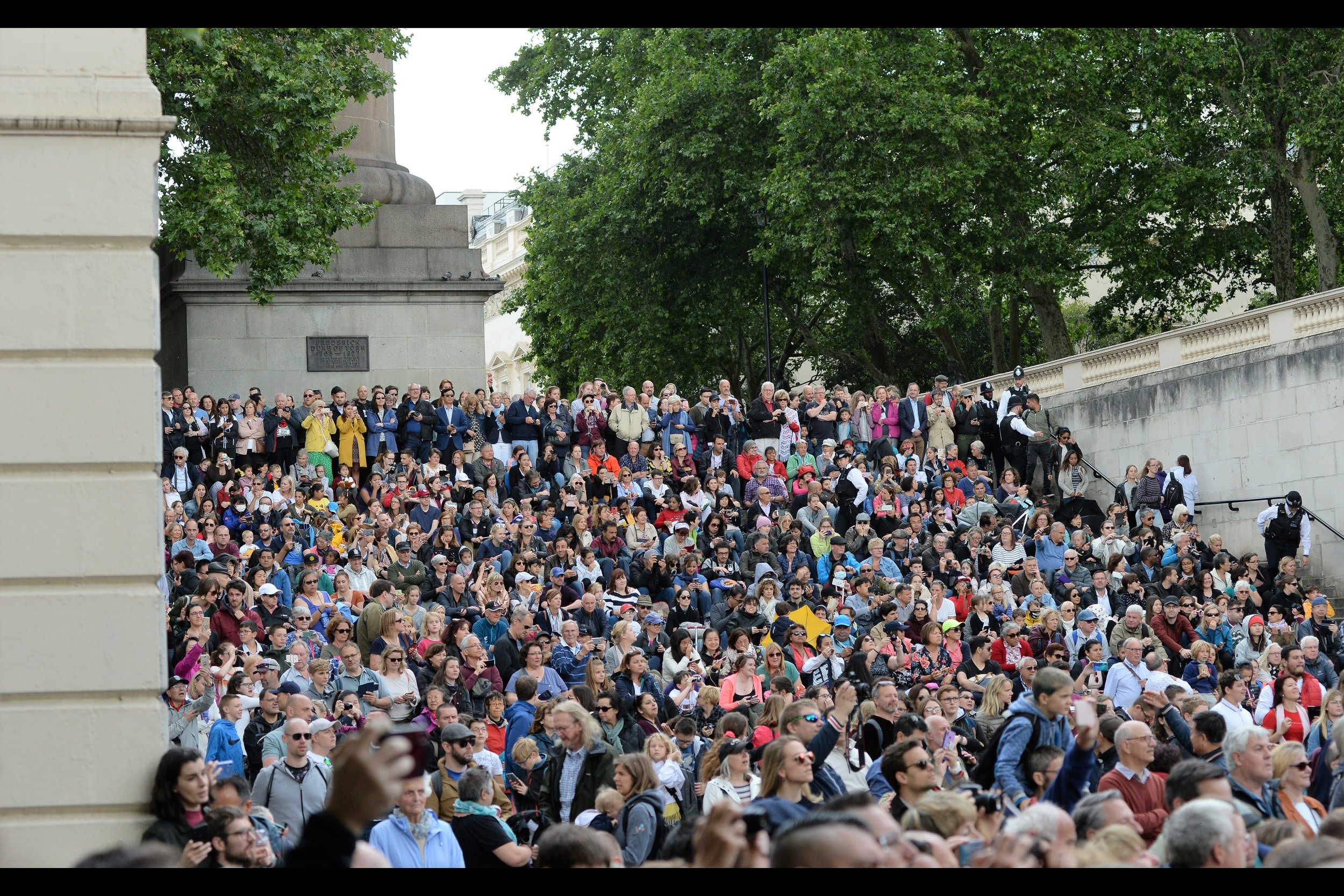 The crowd on the stairs is sadly missing That Guy from last year who had a giant banner that claimed Queen Elizabeth's coming was foretold by the Bible. (As opposed to the published programme for Trooping The Colour, which is available online)