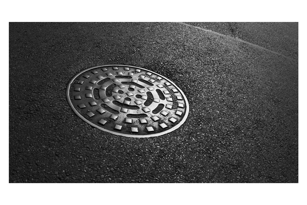 """8. GEORGE STREET  - I was struck by how it was basically impossible to conceive of any original shot to take on this street… so I kind of settled on something unusual rather than aesthetic : a manhole cover at the very end of the street. Art? (Please tell me it's """"Art"""")  On Reflection : … I'm not sure. Maybe a monopod shot might have worked better. Or a wider angle - but it's kind of a busy road (which is not an excuse a REAL photographer should use, I expect."""