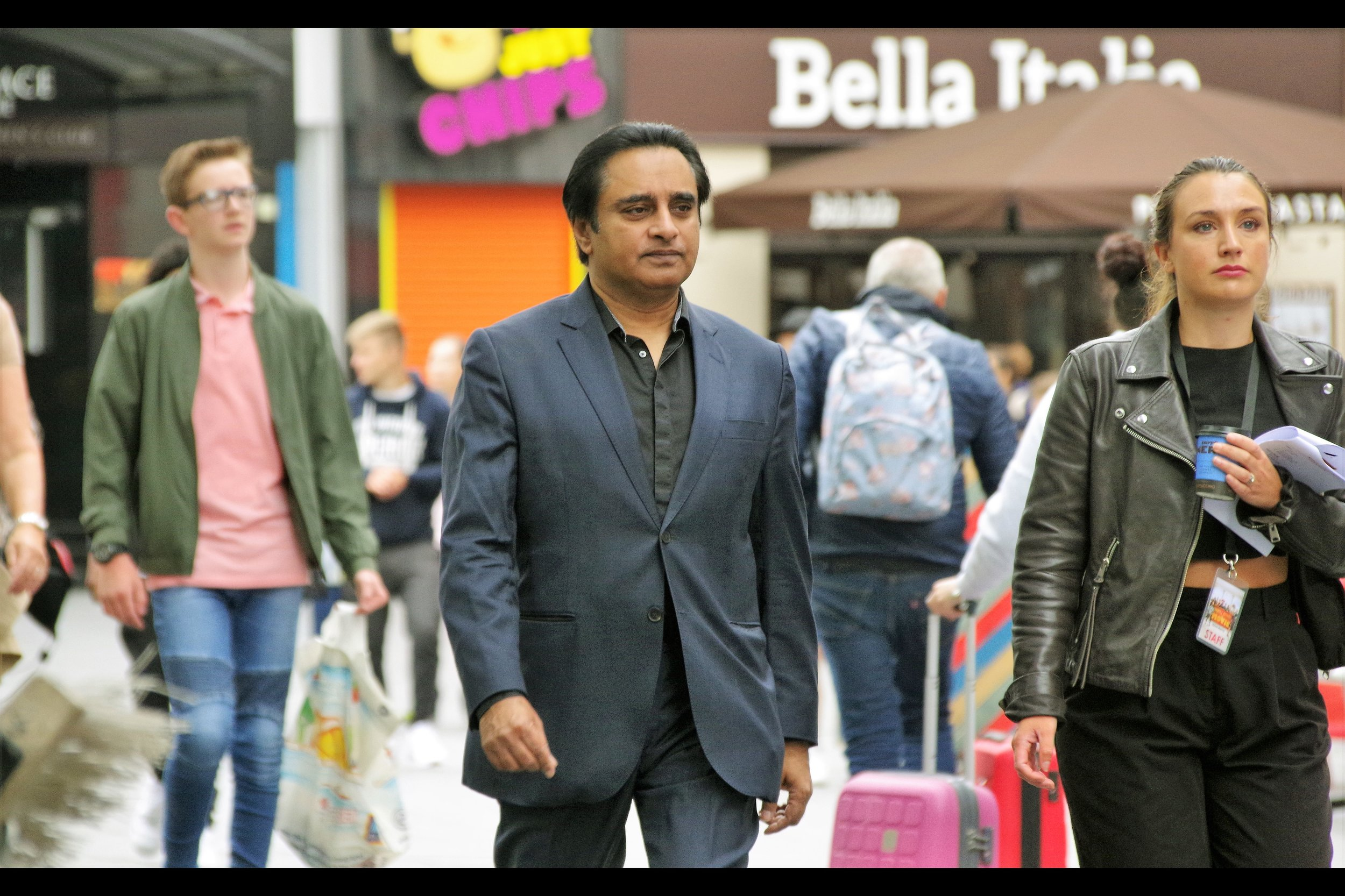 "Sanjeev Bhaskar is best known for any number of things on British Television that I have not seen, and was in the movie ""Yesterday"" whose premiere I missed, and is in this movie in an unspecified role. (The pink suitcase in the background is of uncertain purpose.)"