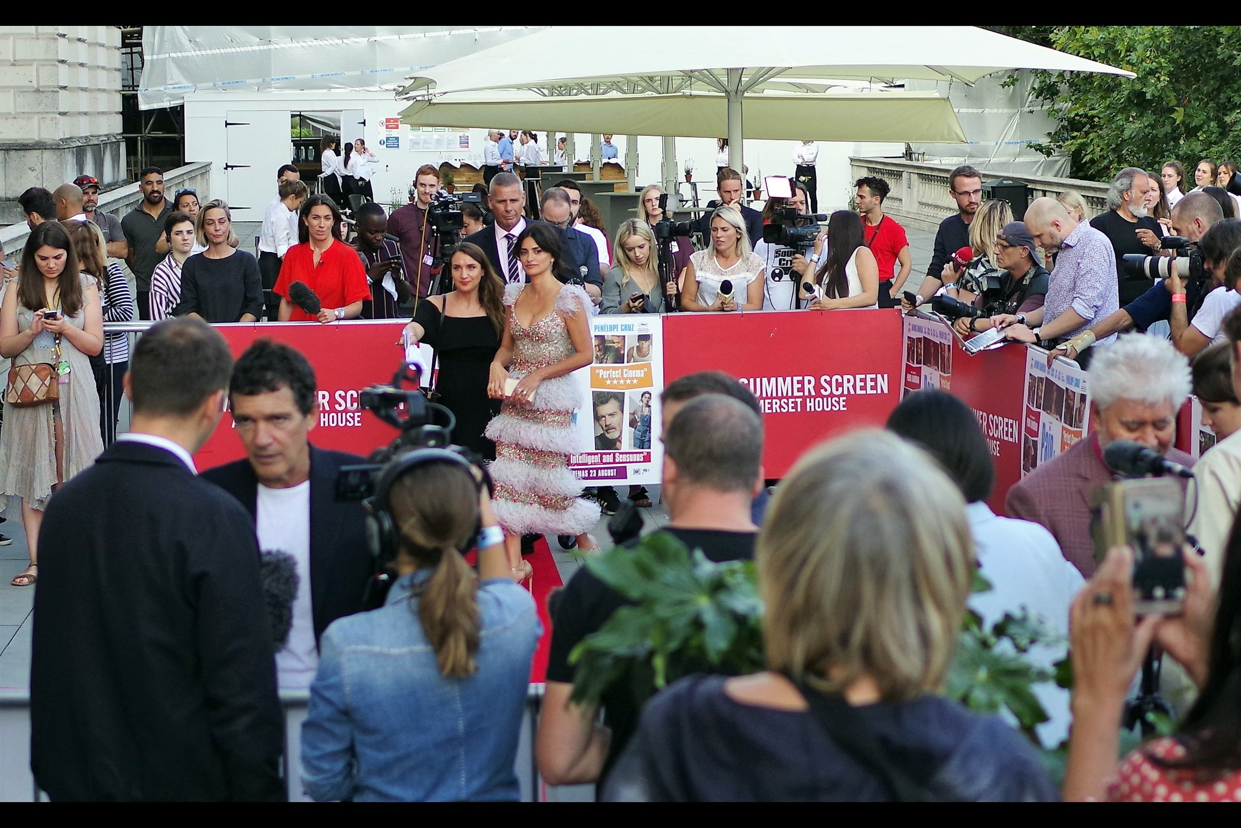 If you can tear your eyes away from the blurry Antonio Banderas in the foreground ( ,…. ladies,   ) - Penelope Cruz might finally have finished doing interviews at the far end and could be moving over here. And I might take another sip from my San Miguel as she makes her way over.