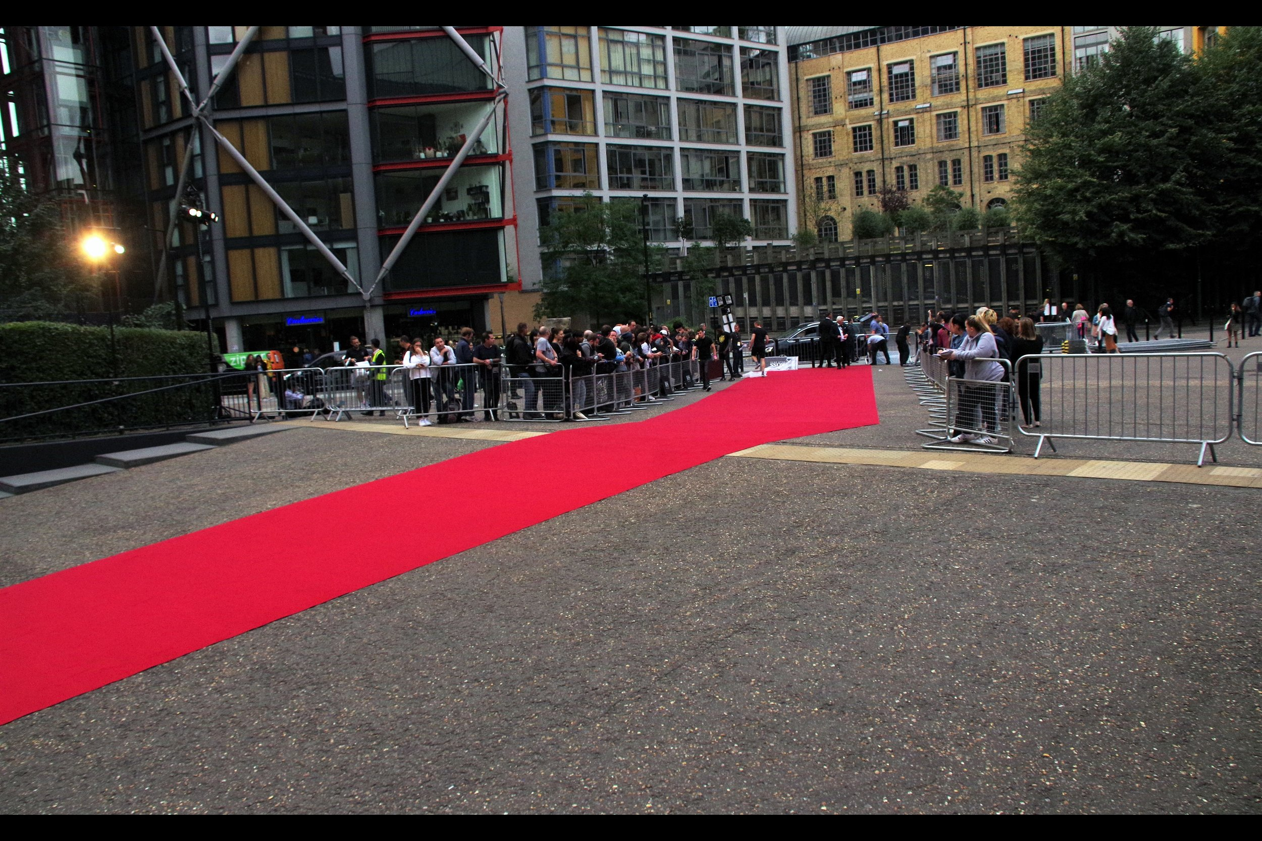 "The red carpet for this event stretches from ""the left of this photo over there"" <gestures vaguely> to the roadside dropoff near the nest of Dealers (and some Fans) on the back-left, where the Paparazzi (currently not yet in place) will face them, in a battle for the ages."