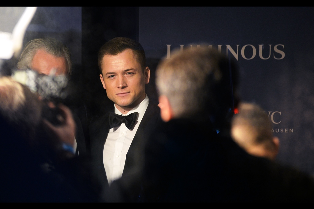 Taron Egerton is winning this battle of wits and wills… and maybe it's the fact that he's wearing a tuxedo and I'm wearing a khaki green t-shirt under a black ski jacket, but I'm not going to contest this. And that Robin Hood (2018) movie he was in… was actually kind of hilarious in a good way.