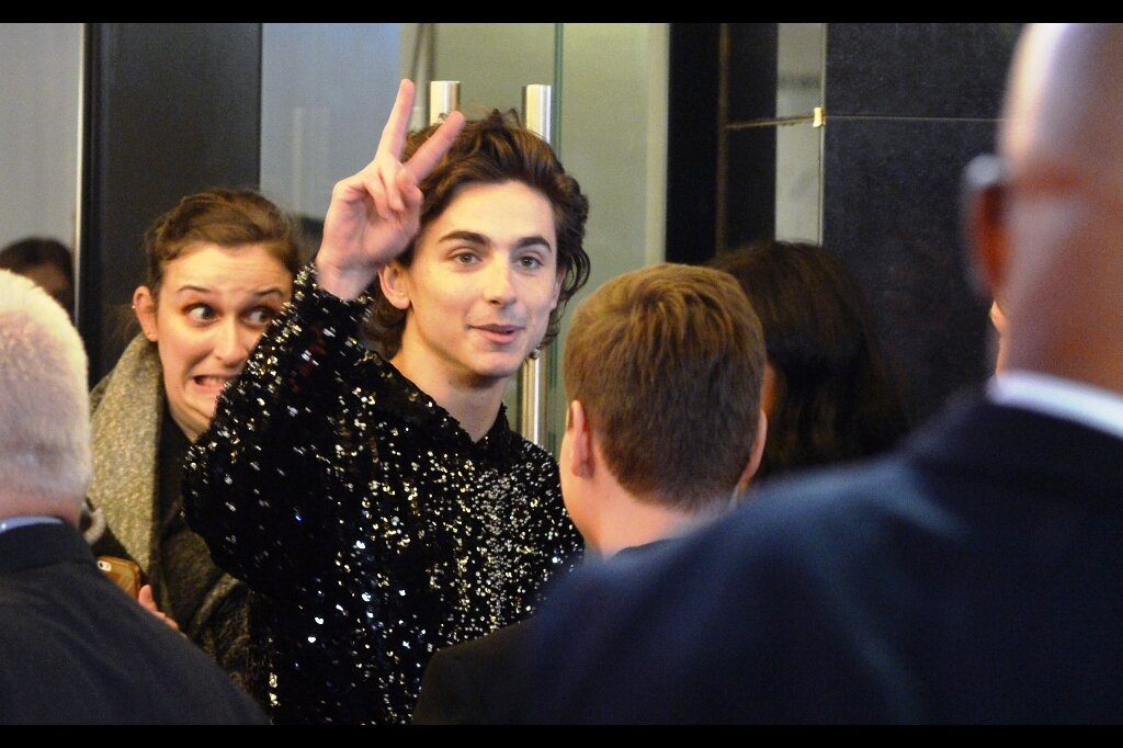 Timothee Chalamet begins to wave goodbye in our direction, and the lady behind him seems only mildly excited about being so close to him without riot barriers between him and her.