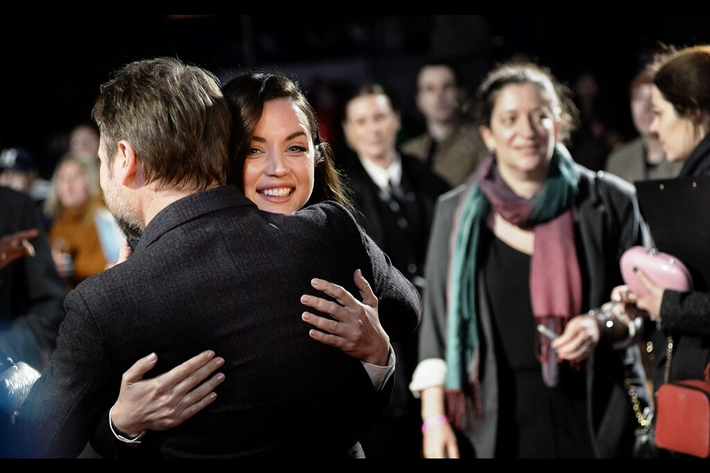 """It's 23:57 as I'm typing this (or, if my boss is reading this, it's 20:57 as I'm typing this), and right now I'm just thinking  """"Ana De Armas is hugging a man who made a movie I don't like, and she's looking at me while doing it, and I'm STILL to a large extent distracted by the woman in the background with that weird cerise and turquoise scarf even though I already used photoshop to both partially blur AND desaturate her. """" Life isn't so much unfair as it is… kind of strange."""