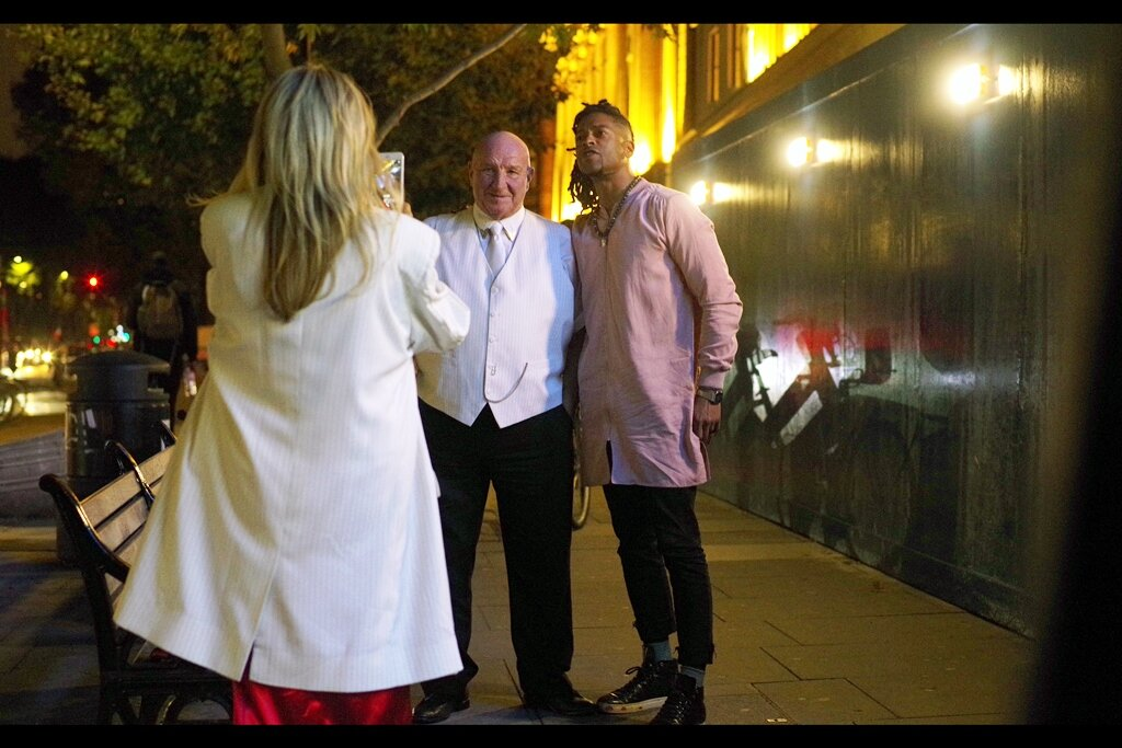 """""""Darling, take a photo of me standing next to this young rapper."""" """"Actually, I'm a practising endocrinologist."""" """"Maybe, but when I update my Facebook profile picture you won't be""""  The man in the white vest is in this movie - he's Dave Courtney."""