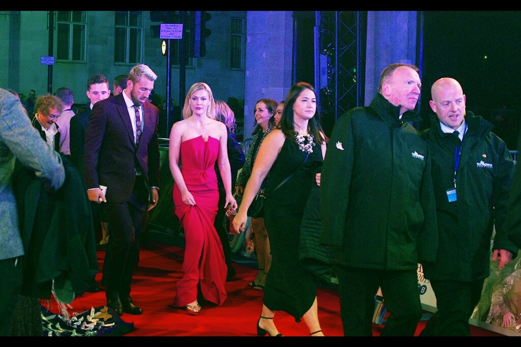 Camilla Kerslake seems ambivalent about the difficulty of correcting the white balance in this photo when everything is/was mostly red, including the ACTUAL red carpet and her dress. Security on the right appear to be concerned about something, but sadly I'm certain it's not about the difficulty of establishing white balance in this environment.