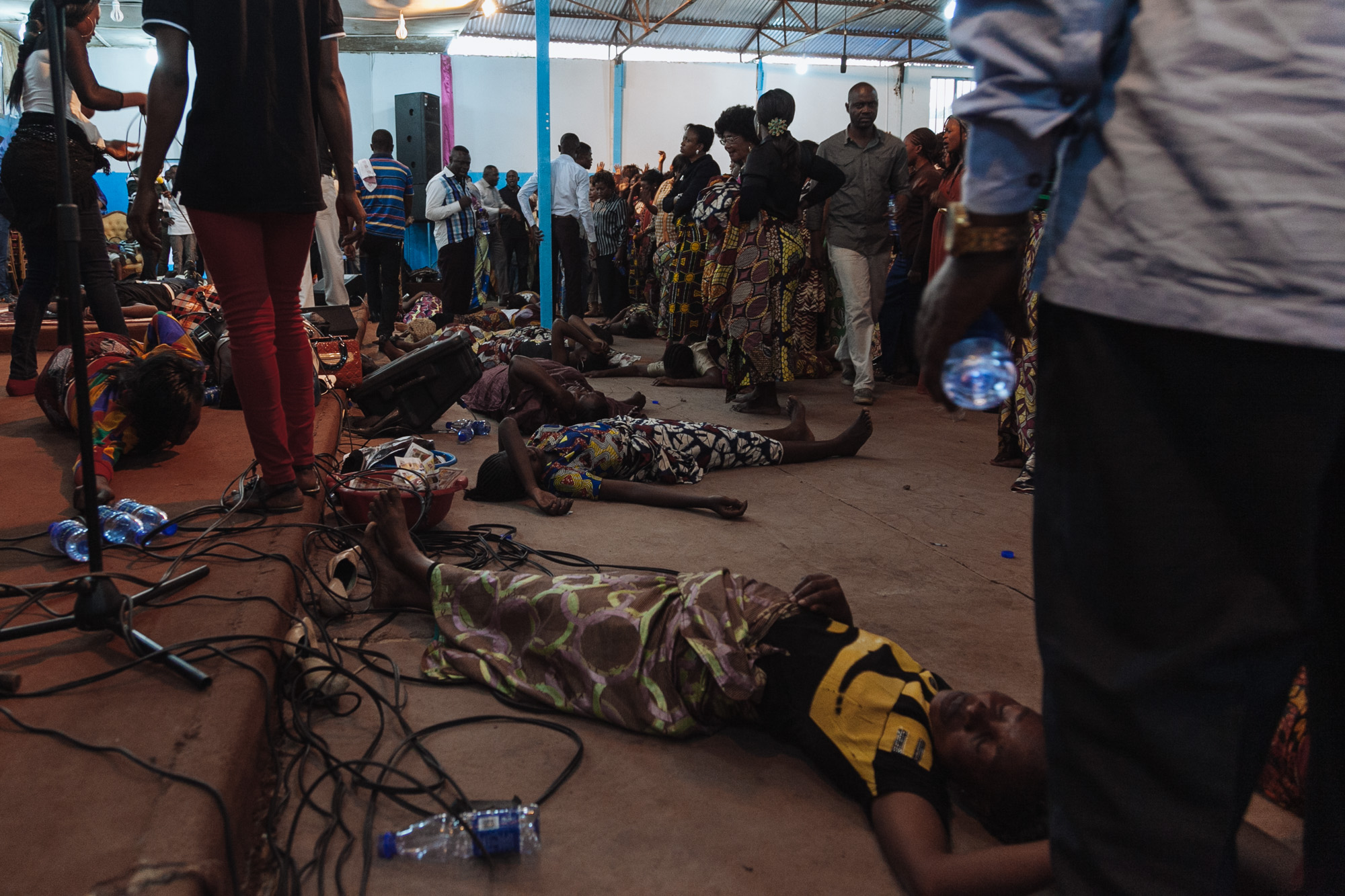 Women lie on the floor of an Evangelical church in Lubumbashi after they fall into uncontrollable fits after believing they have 'caught the holy spirit'.