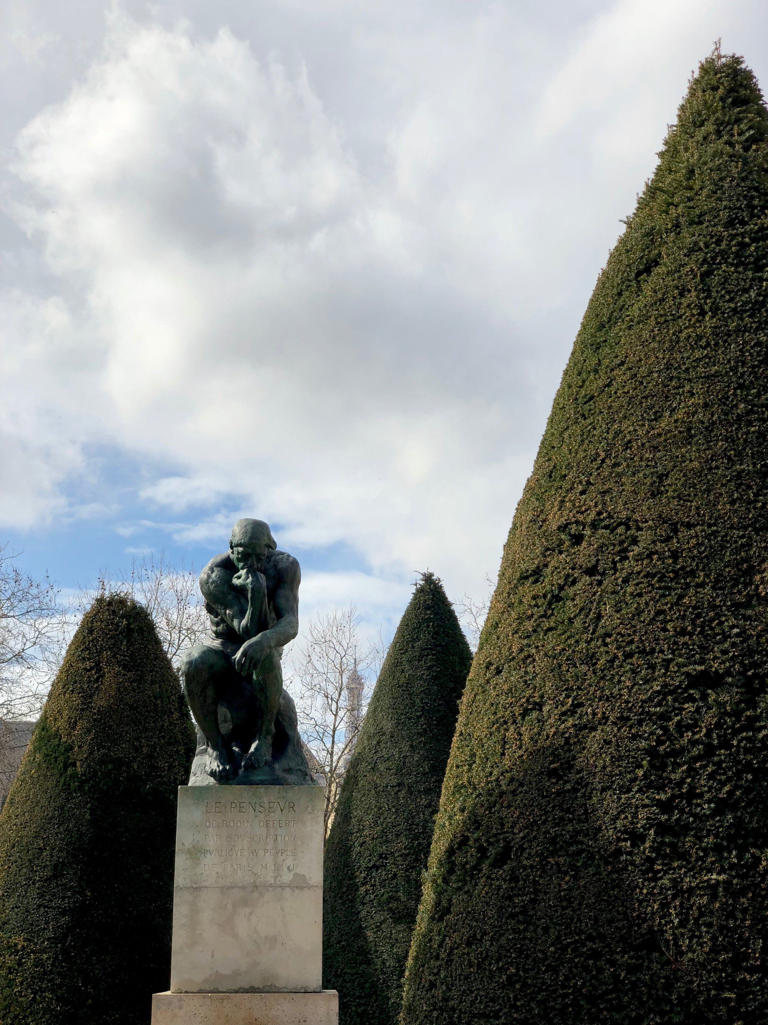 The Thinker, with the Eiffel Tower in the distance.