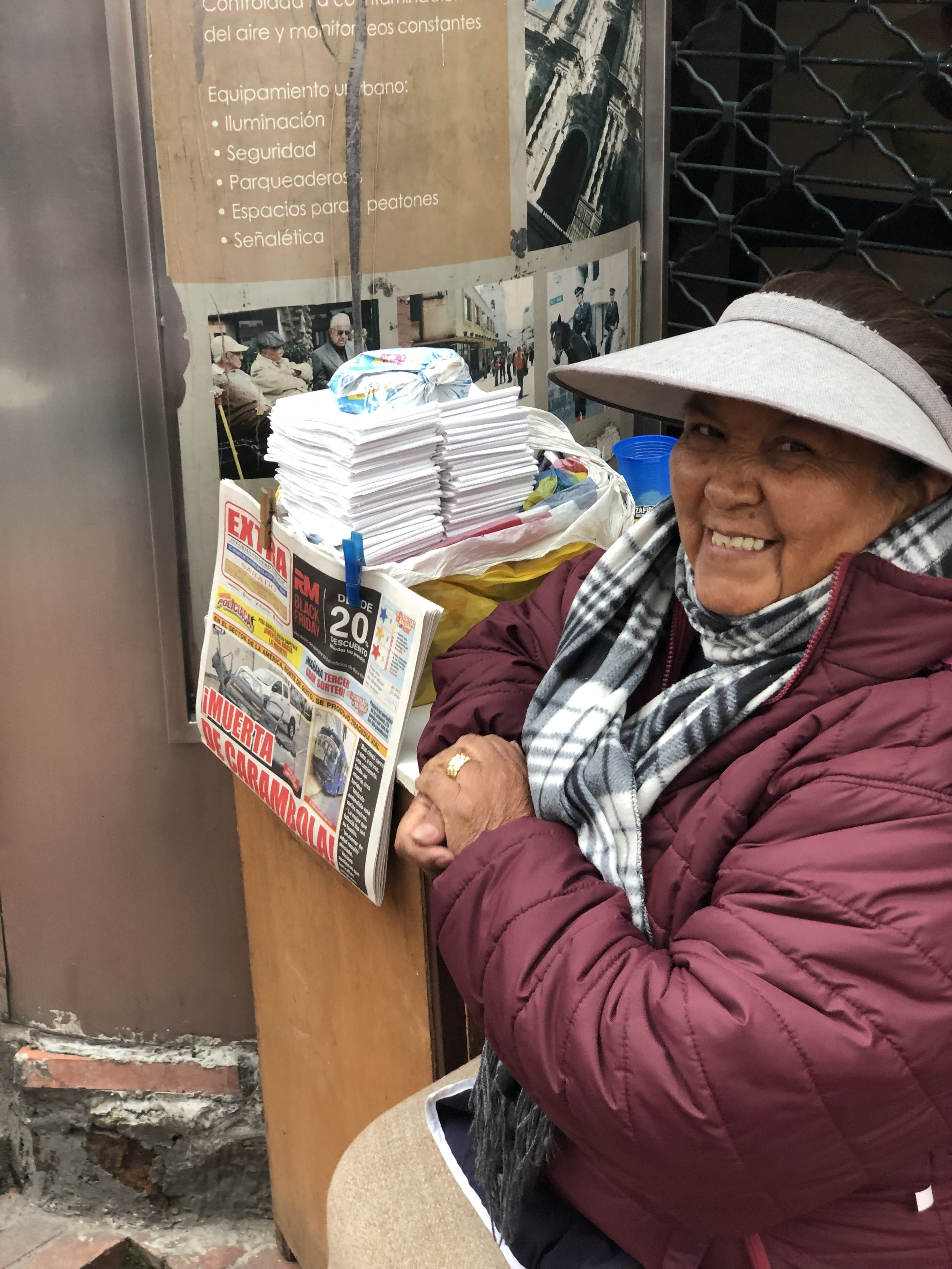 """A lady selling """"napkins"""" outside a public restroom."""