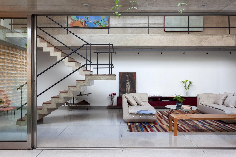 Pé-direito duplo da sala de estar com piso e escada em concreto aparente e piso de granilite. Ao fundo, trilho de iluminação. À esquerda, cobogó amarelo.
