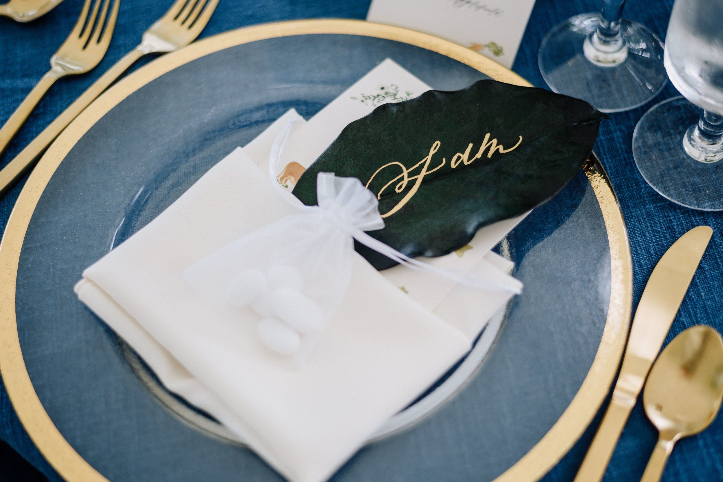 Hand calligraphed magnolia leaf place cards by sable and gray