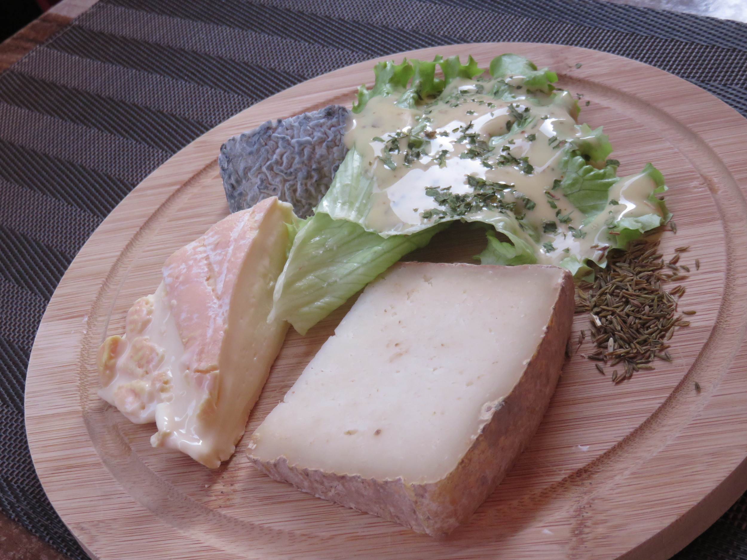 Cheese plate at Aux P'tits Crocs. The big slab is  tomme d'Alsace . From there, clockwise, is the munster,  chèvre cendré  (goat's cheese with ash), a salad, and cumin seeds for the munster.