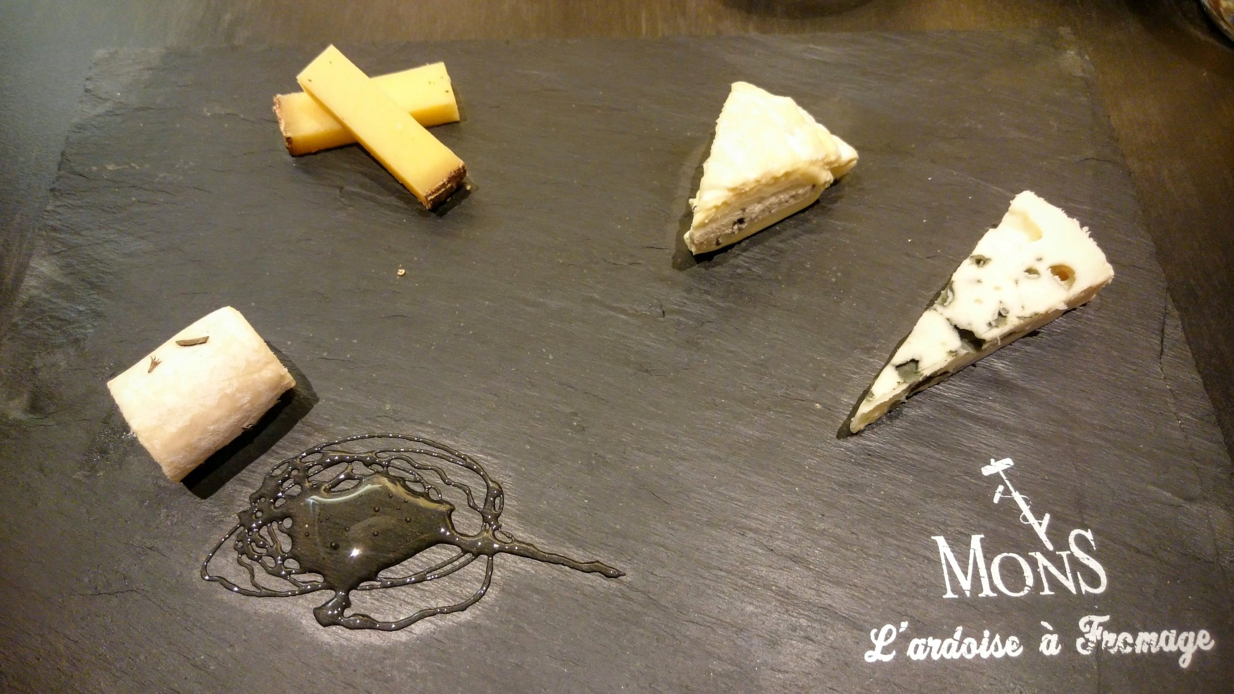 From right to left: a young chèvre with truffled honey, a 24-month comté, Saint-Marcellin with a truffle cream, and Roquefort.