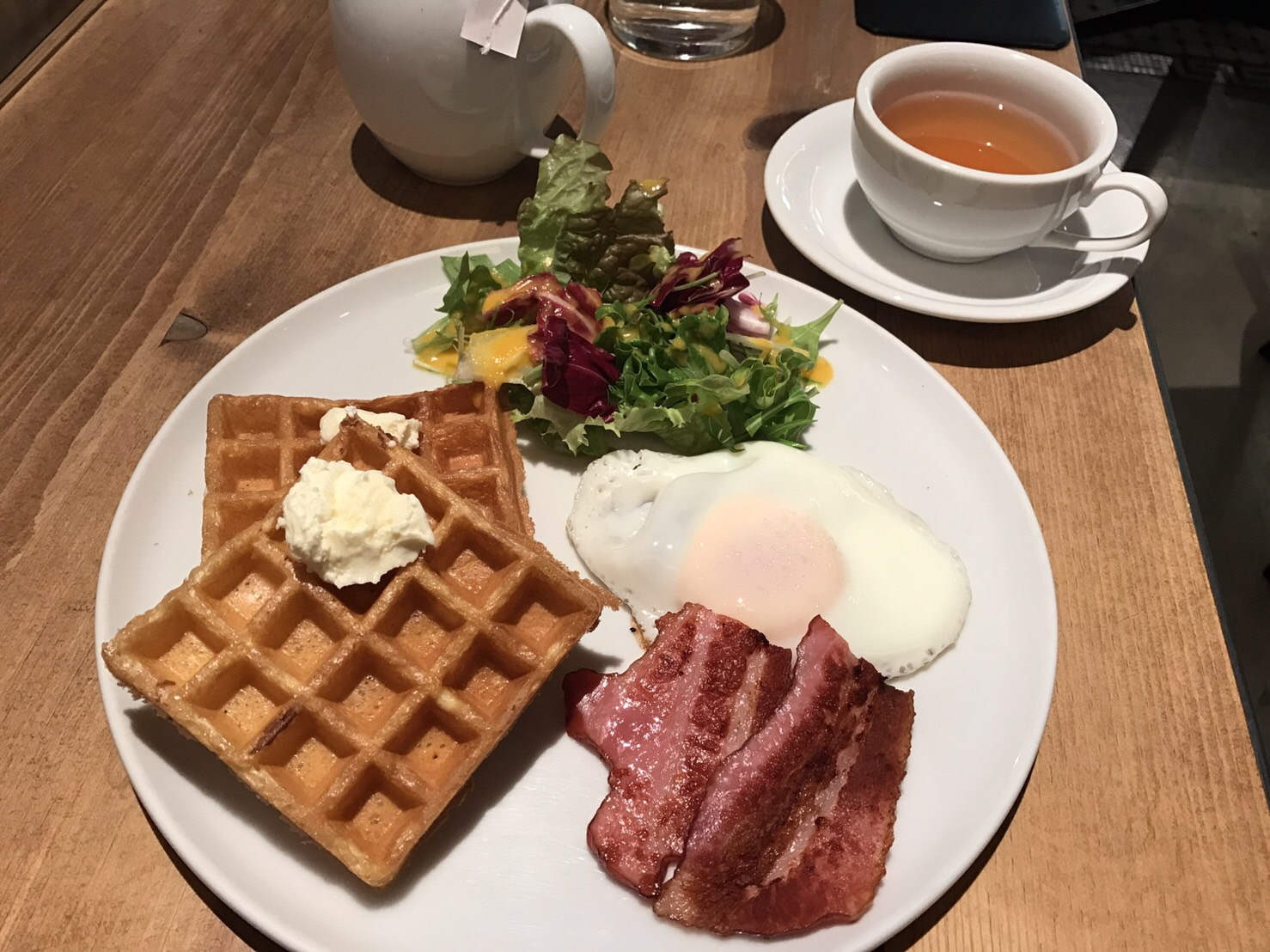 Waffles, an egg, salad and bacon for breakfast