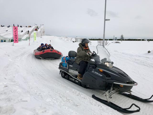 Ride a raft behind a snowmobile