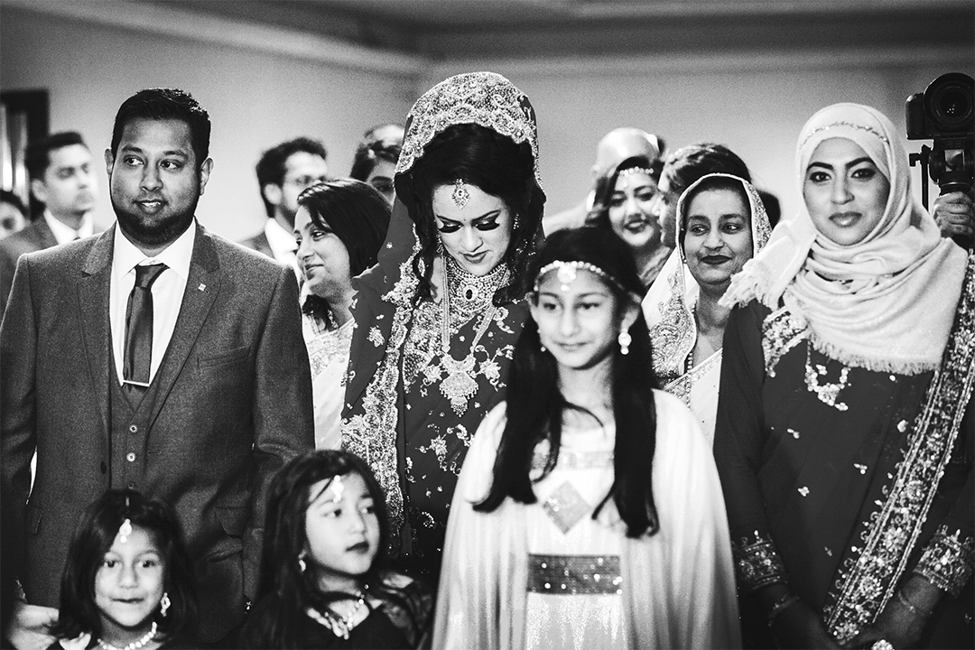 Entering the Walima  The bride and groom enter the Walima together and make their way to the stage at the back of the room, overlooking all of the guests, who are seated at tables ready to eat.
