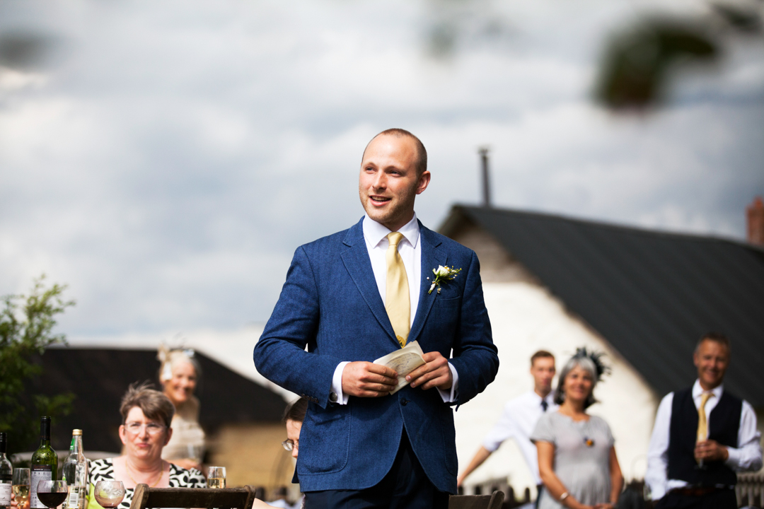 best man gives speech outdoors