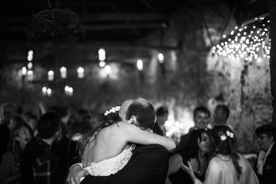 bride and groom hug by candlelight