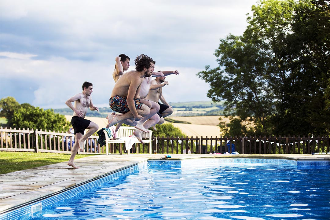 groomsmen jump into swimming pool