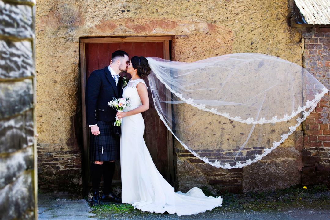 bride and groom kissing The Oak Barn Hittisleigh