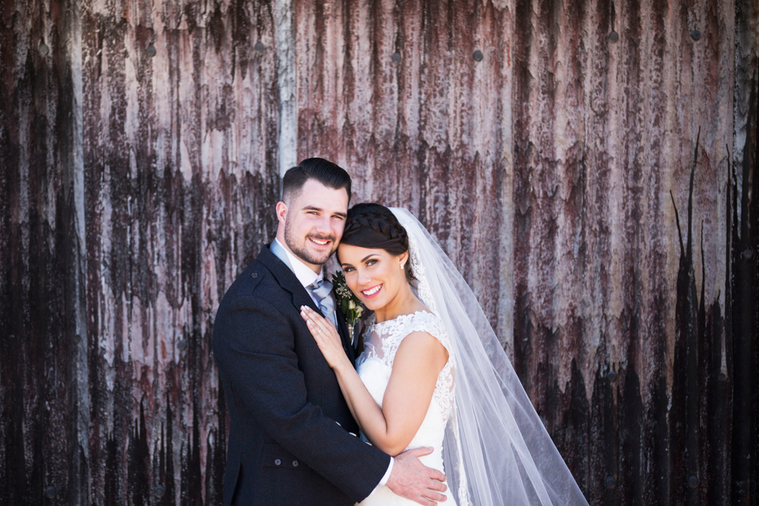bride and groom posing against corrugated backdrop