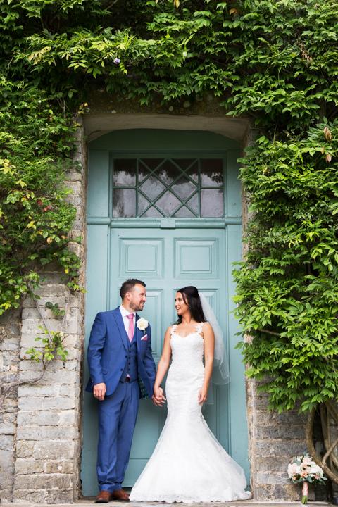 bride and groom posed under doorway Kingston Estate Devon