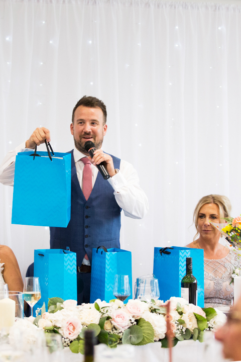 groom hands out gifts in blue bags