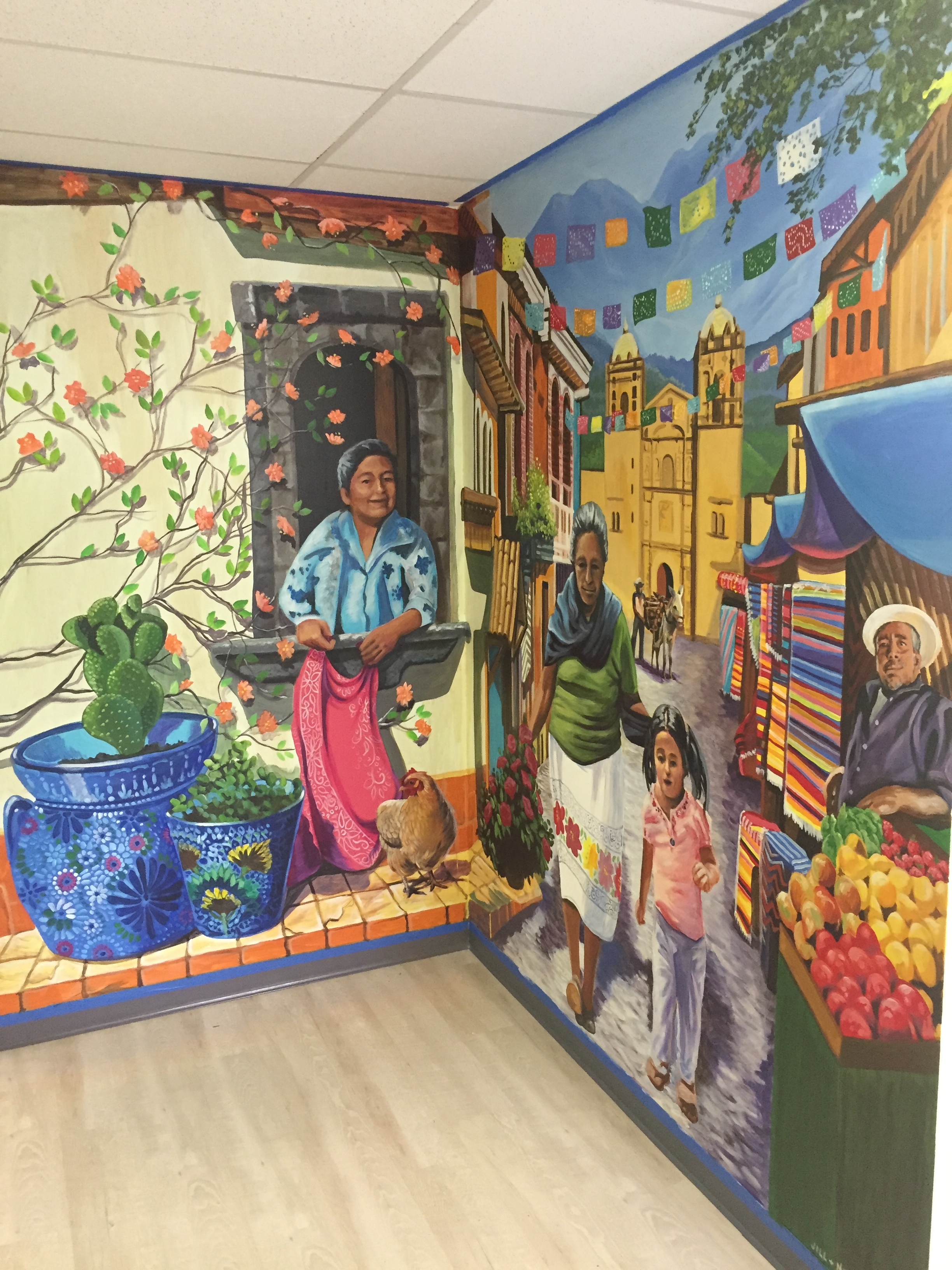 Spreading the mural across a corner of the room helps to make it feel more immersive. From the right viewpoint, you can almost hear the church bells and smell fresh mango from the fruit stand.
