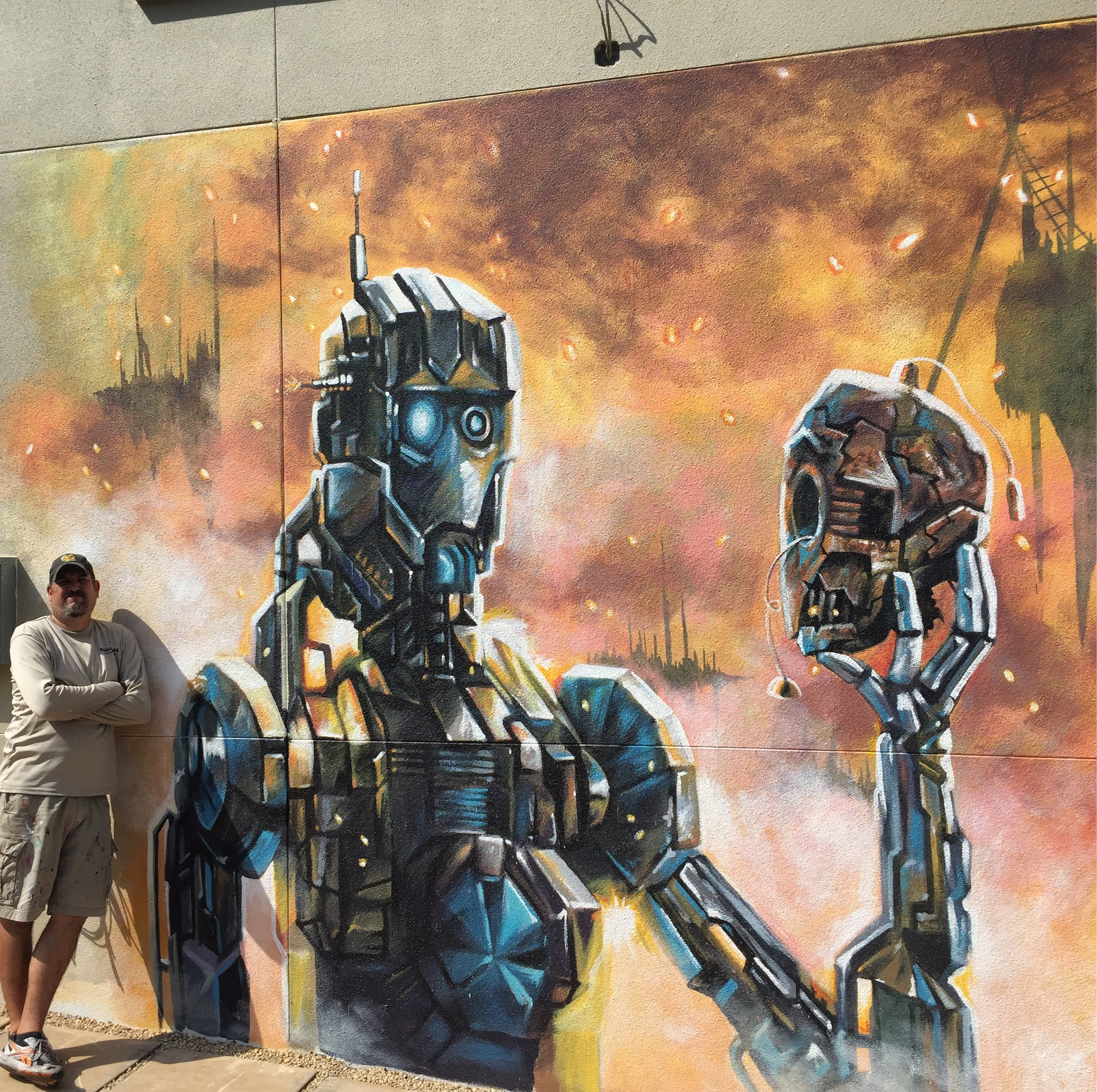 Finished Robot Hamlet picturing Hector Diaz who assisted on the project. The mural was painted on the exterior wall of the Kretzmer Building in Sarasota, FL for Florida Studio Theatre.