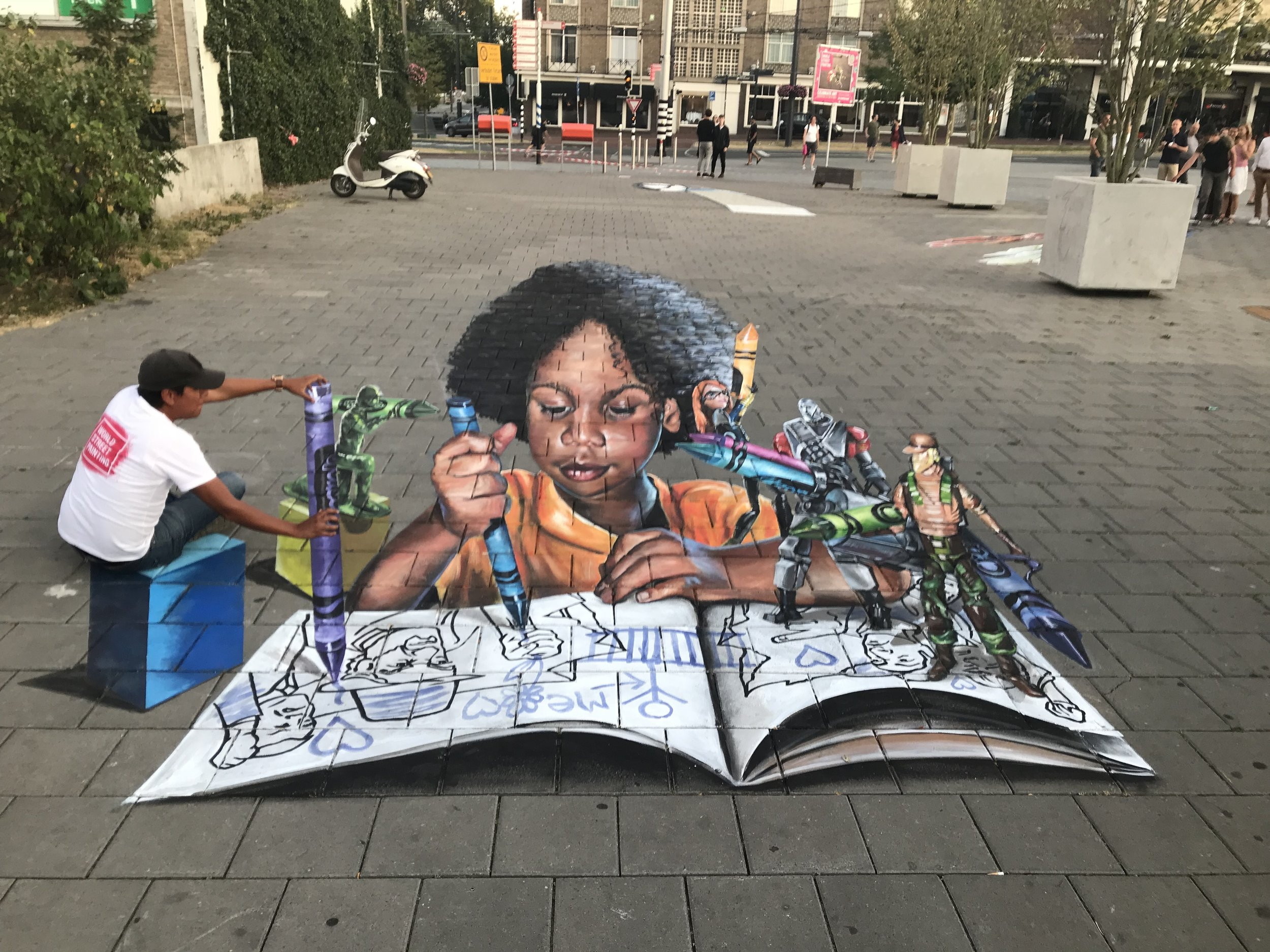 3D Street Painting of a boy solving war and violence in a coloring book with creativity at the World Street Painting Festival in the Netherlands.
