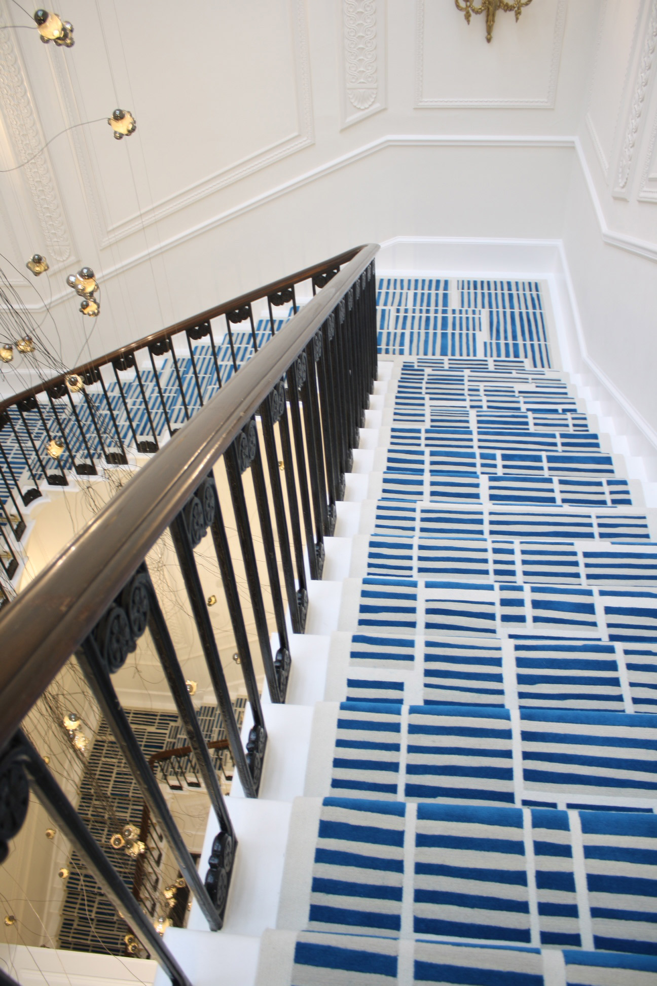 The cascading1829 staircase is enhanced by a contemporary handtufted carpet. CMI created a carpet design from original artwork by Vancouverartist Elizabeth McIntosh. Photo: ©Creative Matters