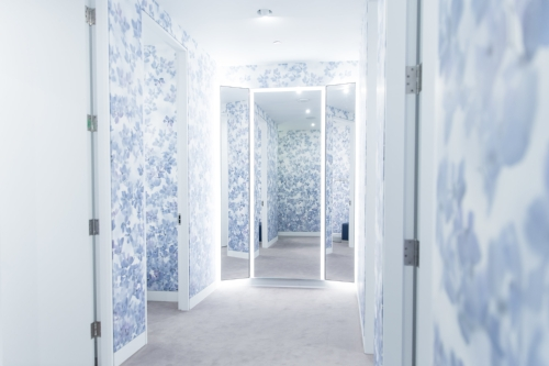 In the women's fitting rooms, we created a modern feminine ambience with a custom Creative Matters wallcovering design. Photo: Jenna Marie Wakani