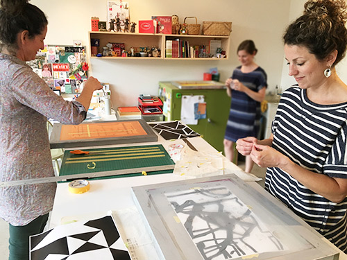Sandra (right) and Leah (left) screen print the scrims.