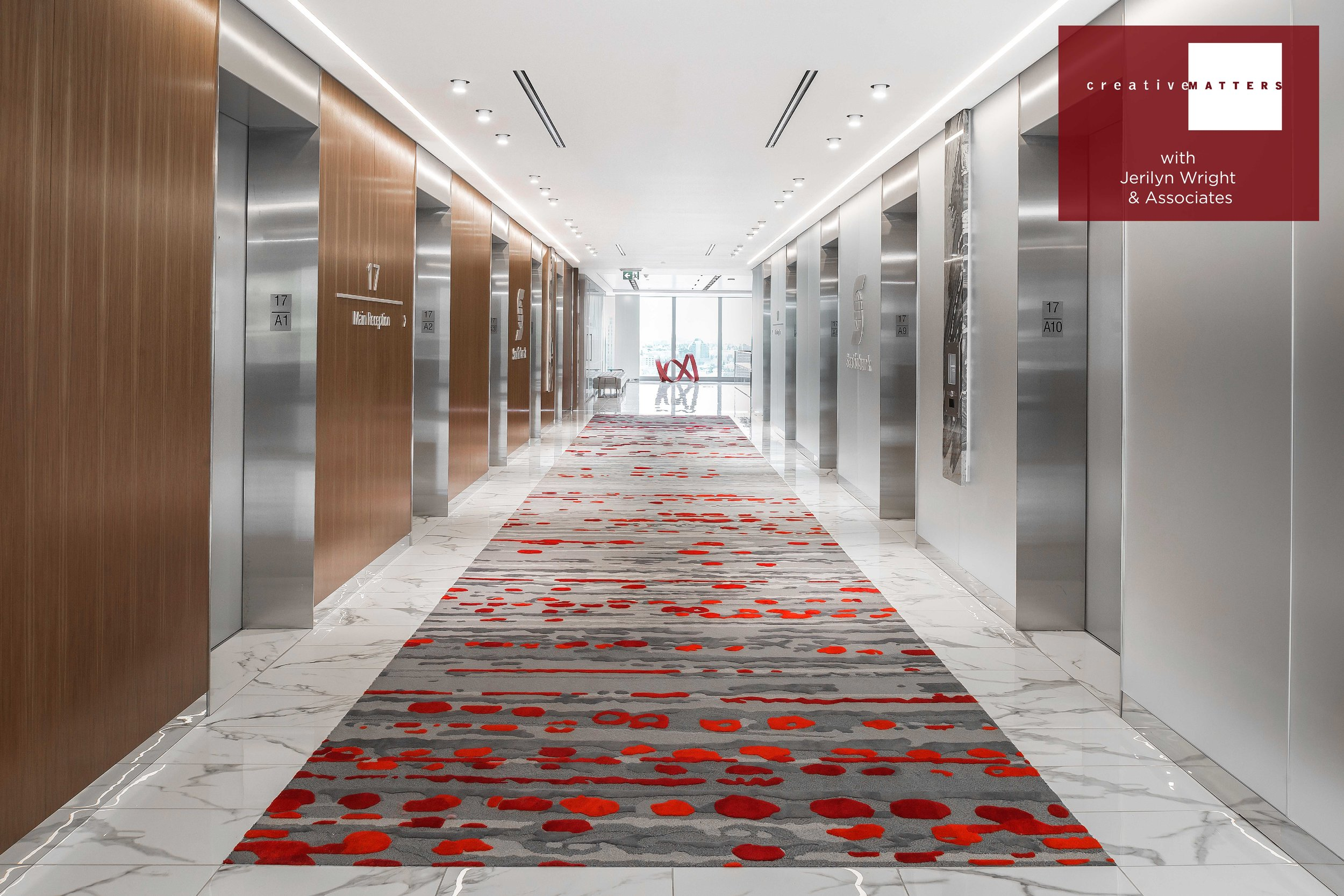 A tactile experience awaits those who step out of the elevators and onto this highly textured inset runner. The bank's logo colour literally pops because the red details are all higher (7mm) than the sophisticated greys in 5mm and 6mm loop pile and 6mm cut pile. Connecting to the marble of the floor and the varying shades of metal, there is a beautiful gradation of dark greys at the two short edges to a lighter grey in the centre. In addition to the pile height drama, the 11 colours in 100% wool add warmth and dimension to the simple but polished space. All in all, an elevating experience.  Project: elevator lobby runner for a Calgary bank Rug: 100% wool handtufted in Thailand Interior Designer: Jerilyn Wright & Associates