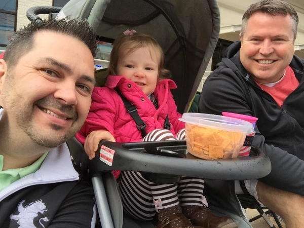 Madison and her dads watch the Pegasus Parade