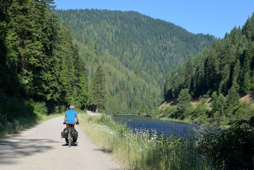 Bob rides along a river.