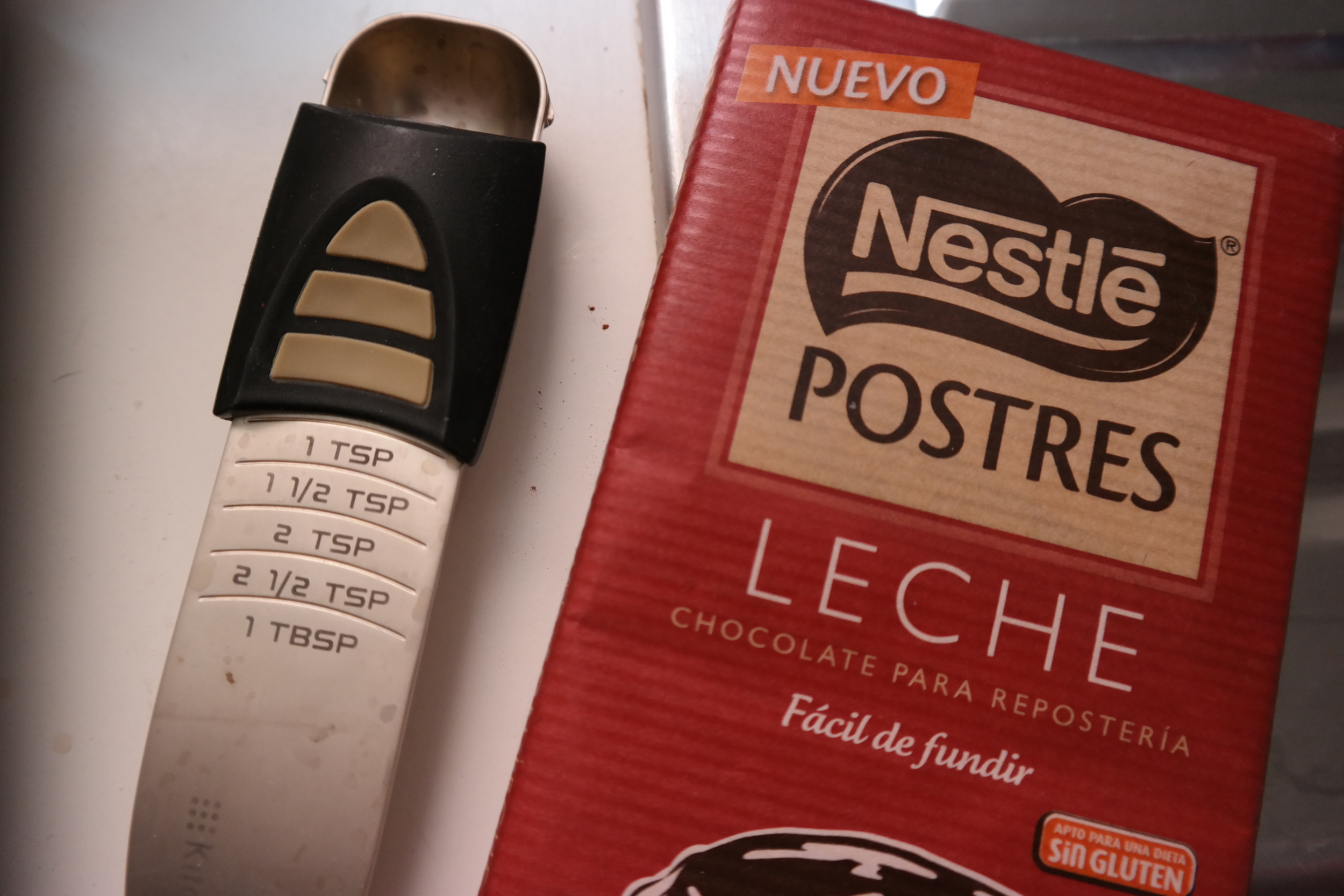 """I didn't end up using this chocolate for the icing, which I'd originally intended to do (I skipped the icing part), but I know some of you like seeing products here so I included it. This is milk chocolate for baking, """"Easy to Melt."""" Also, I'm SO glad I remembered to bring this multi-measurement measuring spoon, because measurements are different here. Not to mention, it was compact in my luggage!"""