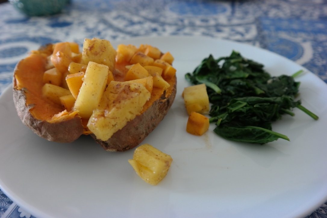 Baked sweet potato, topped with pineapple and apricot chunks . I put the fruit in a saucepan with some coconut oil, nutmeg, and cinnamon while the potatoes were cooking, and softened them. I sauteed some spinach on the side, and this was a very easy, super delicious meal.